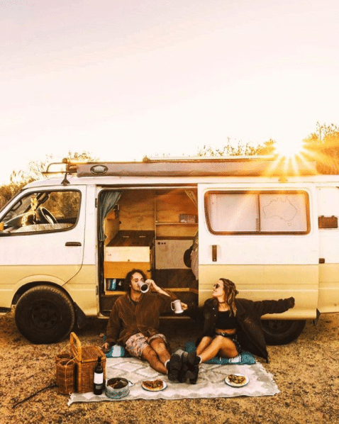 Two travelers enjoy a picnic in front of their van.