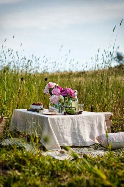 A romantic picnic set-up in the middle of a field.
