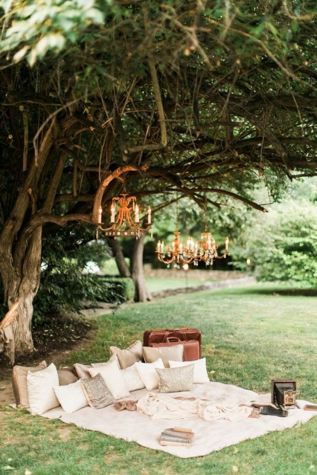 Romantic picnic set-up under a large tree in a park.